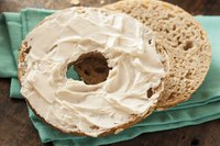 Fresh cream cheese spread over a whole wheat bagel on a cloth napkin.