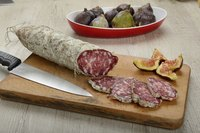 Salame secchi fiore on a cutting board with figs.