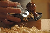 Woodworker shaving a piece of wood with a block plane.