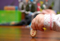 Little girl's hand spinning dreidel