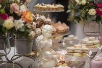 An assortment of decadent desserts on a table with flower arrangements and a romantic sculpture.