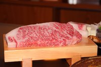 A slab of Kobe beef on a cutting board.