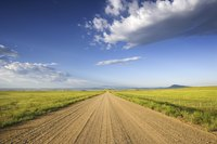 Calcium chloride controls weeds and dust that may spring up on a rural roadway.