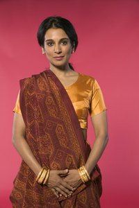 A saree blouse is worn underneath the saree wrap, which goes around the lower half of the body and over the shoulders.