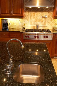 The dark look of Uba Tuba granite pairs well with a neutral-colored travertine backsplash.