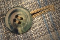 Threads in four-hole buttons may be sewn parallel or crossed.