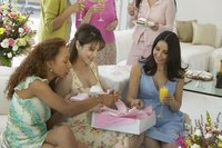Group of women at a baby shower opening a gift.