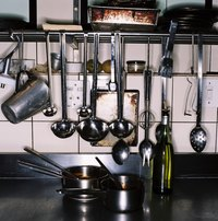 Increase your storage space in a galley kitchen by hanging utensils from rails.
