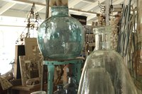 A close-up of large glass vessels and other items at a flea market.