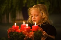 A child is holding an Advent wreath.