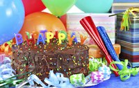 A birthday cake with streamers, balloons, noise makers and presents.