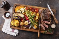 Grilled red meat and vegetables on a cutting board with seasonings.