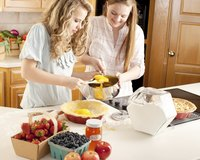 Two teenage girls cooking in kitchen