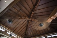 Two spinning ceiling fans in a the peak of a wooden ceiling.