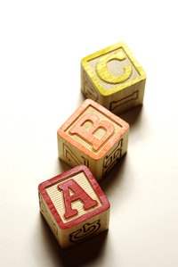 Alphabet blocks can be stacked into simple shapes.
