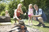 Roasting hot dogs over open flame brings families together.