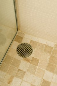The shower drain is at floor level, so the drain pipe must run beneath.