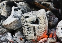 Hardwood coals provide slow, even heat for pit cooking.