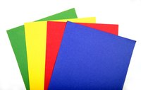 Use construction paper in primary colors to make spots for a cardboard Twister costume.