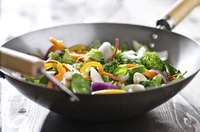 Fresh vegetables in a wok on a wooden table.