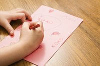 Young child making a Valentine's Day card.