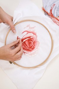 Add a finished cross-stitch design to a decorative pillow.