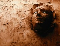 Clay head emerging from a wall.