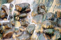 Small stones add earthy elements to a miniature waterfall.