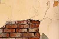 A cracked plaster wall can reveal the bricks underneath.
