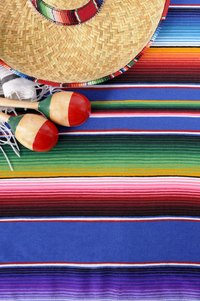 Accessorize tables and chairs with Mexican blankets and hats.
