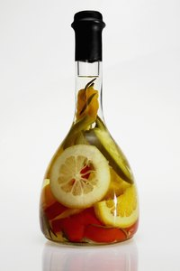 Assorted fruit and vegetable slices turn into kitchen decor when placed with oil in a bottle.