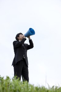 Grip the megaphone around the mouth section and talk into it to amplify your voice.