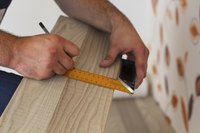 Man measuring and marking laminate floor