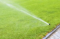 A sprinkler irrigating a green lawn with water.