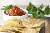 A bowl of picante sauce served with a bowl of tortilla chips and fresh cilantro.