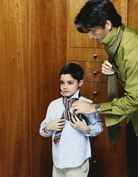 Tying a necktie is an imposing task for a young boy.