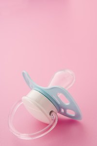 Integrate a pacifier with a looped handle into the mom-to-be's corsage.