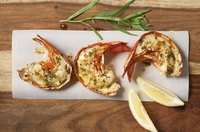 Dress halved lobster tails with herbed butter and lemon juice after broiling.
