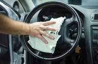 Image of a man using a microfiber towel to clean his steering wheel.