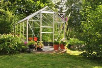 A small greenhouse in a backyard.