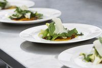 Three small salads on little white plates