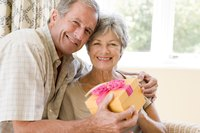 Mature married couple holding a wrapped gift box
