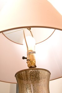 Use paint or wallpaper to darken your fabric lampshades.