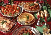 Assorted holiday buffet dishes on a red tablecloth.