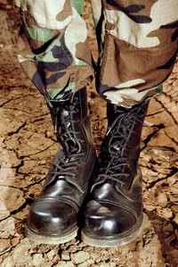 Transform a pair of army boots into a set fit for a professional wrestler.