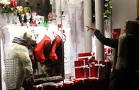 A woman pointing at a Christmas window display in Paris, France.