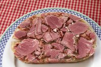 Sliced piece of head cheese on plate.