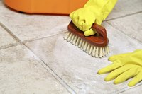 A close-up of a person wearing gloves while scrubbing a tile floor.