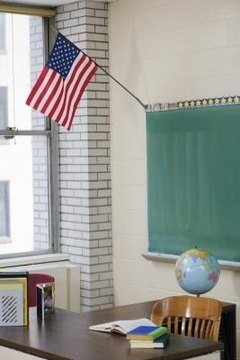 An American flag at the front of a school classroom is a common sight.