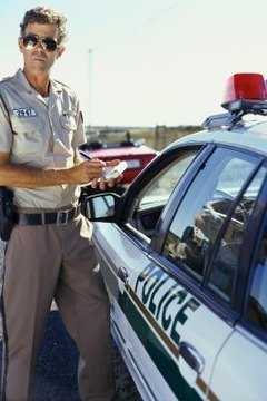 A traffic ticket is given by a police officer on duty.